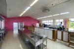 厨房からのカウンターに客室。ピンクの仕切壁